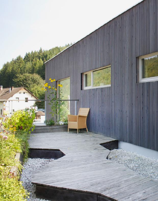 Moderne Fassade aus Lärchenholz mit Dachterrasse und Dielenboden samt Pflanzbehältern in Lärche