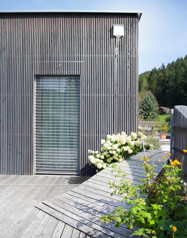 Holzfassade in elegantem silbergrau, Holzterrasse mit Steg, Zaun und Pflanzbehälter