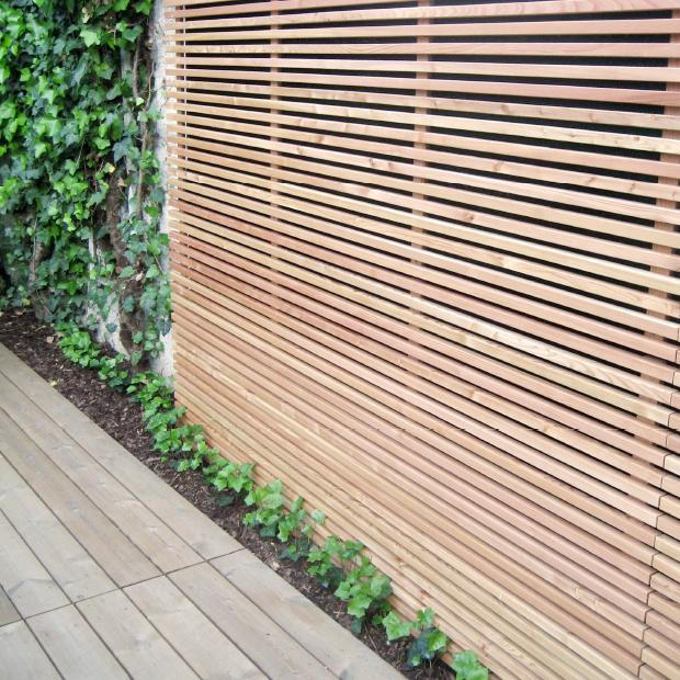 Moderne, elegante Sichtschutz-Wand aus Lärche mit horizontalen Leisten / Lamellen