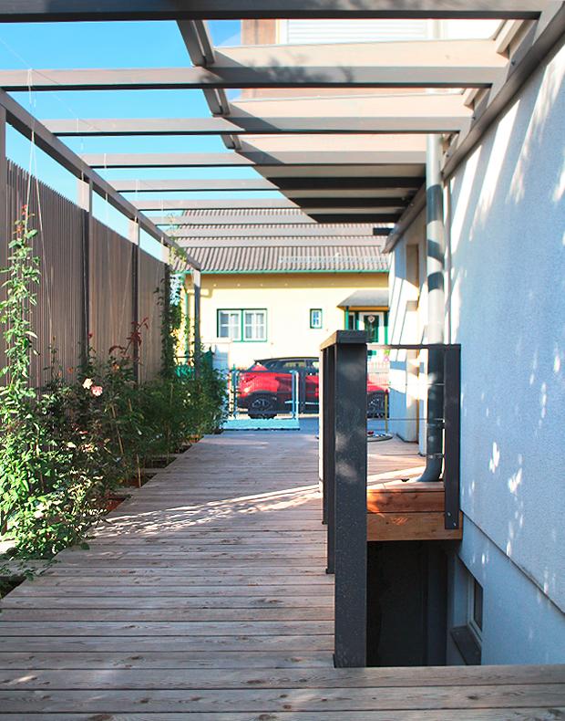 Modern und zeitlos in Holz: Pergola in Lärche grau geölt mit transparentem Sichtschutz mit vertikalen Lamellen / Holzleisten