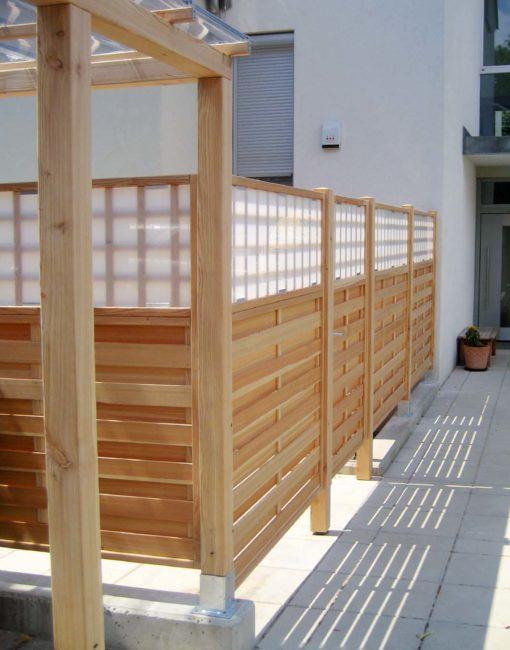 Dichtzaun mit Rankgitter und transparentem Plexiglas als Sichtschutz auf der Terrasse
