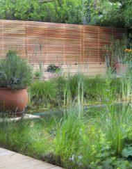 Lauschiger Innenhof mit horizontale Holz-Lamellen in Lärche natur als Sichtschutzzaun