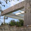 Moderne Terrassenüberdachung in Lärche mit Glas und Leisten / Lamellenfassade aus Holz