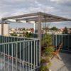 Puristisch und modern: Pergola / Laube / luftiger Pavillon für Dachterrasse aus Holz mit Glas und Textil-Beschattung
