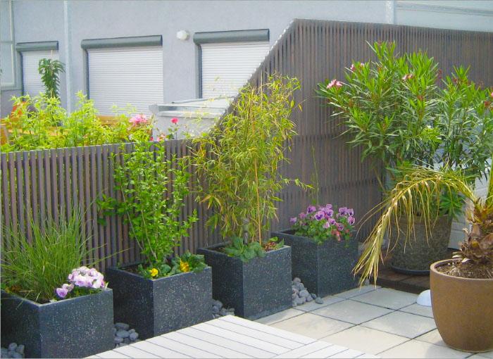 Moderner Gartenzaun mit Leistenfelder / Lamellen als Sichtschutz auf der Terrasse in Lärche Steingrau