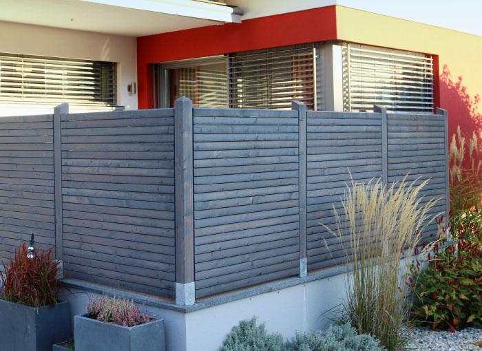 Hält unerwünschte Blicke fern: Holz-Sichtschutzzaun Lärche Grau auf der Terrasse